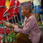 Au marché, une vendeuse de riz gluant cuit dans du bambou.