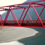 Au milieu d'une vallée entre le bleu profond de la rivière et le vert sombre des épineux : le rouge pétant d'un pont !