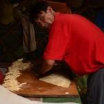 """Un homme coupe une pâte pour en faire des pâtes, plat de base de la """"gastronomie"""" mongole"""
